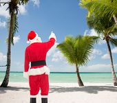 christmas, holidays and people concept - man in costume of santa claus pointing finger from back over tropical beach background