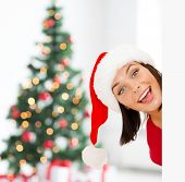 x-mas, people, advertisement and sale concept - happy woman in santa helper hat with blank white board over living room and christmas tree background
