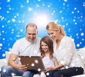 family, christmas, holidays, technology and people concept - smiling family with laptop computer over blue snowy background