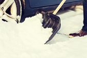 transportation, winter and vehicle concept - closeup of man digging up stuck in snow car