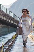 stock photo of runaway  - Bride Walking On The Bridge With Her Suitcase - JPG