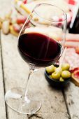 foto of deli  - Glass of red wine with charcuterie assortment on the background - JPG