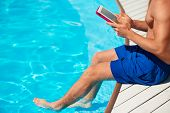 Close-up of man using tablet computer near by swimming pool