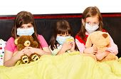 picture of influenza  - Sick children in bed wearing medical masks because of infection with influenza virus - JPG