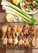 Grilled chicken drumsticks and salad in transparent pot