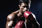 Young Man Looking Aggressive With Boxing Gloves. Caucasian Male Model
