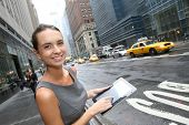 Businesswoman with tablet waiting for a taxi cab in NYC