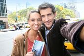 Couple in New York city taking picture with smartphone