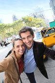 Couple having fun in Manhattan, taxi cab in background