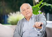 Portrait of senior man holding metal cane while sitting on couch in nursing home porch