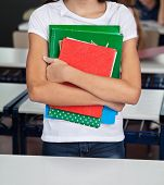 Midsection of schoolgirl smiling while holding books in classroom