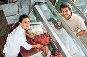 Portrait of female butcher selling minced meat to male customer in butchery