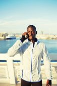 Handsome runner using mobile phone after fitness training outdoors