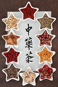 Chinese herb tea selection in star shaped porcelain bowls over brown paper background with chinese calligraphy script. Translation reads as chinese herbal teas.