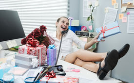foto of office romance  - Female office worker feet up on desk talking on the phone with romantic gifts - JPG