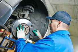 image of levers  - car mechanic worker replacing brakes of lifted automobile at auto repair garage shop station - JPG