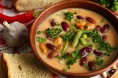 picture of fresh slice bread  - Bean soup in bowl with fresh sliced bread on napkin - JPG