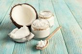 stock photo of spooning  - Fresh coconut oil in glassware and wooden spoon on color wooden table background - JPG