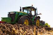 stock photo of plow  - Agricultural tractor plowing a field before sowing - JPG