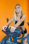 foto of elliptical  - Young sports woman doing exercises on an elliptical trainer in the gym - JPG