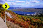 stock photo of pedestrian crossing  - View of a pedestrian crossing sign at the top of Prospect Mountain, Lake George, NY in the middle of autumn while also overlooking the lake and Adirondack Mountain Range. Fall, 2014.