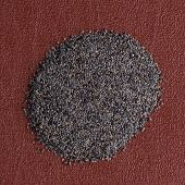 picture of opiate  - Top view of poppy seeds against red vinyl background - JPG