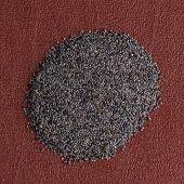 foto of opiate  - Top view of poppy seeds against red vinyl background - JPG