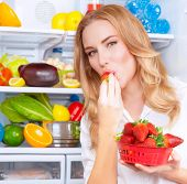 picture of strawberry blonde  - Portrait of a beautiful female standing near open fridge full of fresh fruits and vegetables - JPG
