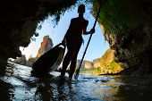 stock photo of cave woman  - Silhouette of the young lady entering marine cave with kayak - JPG