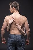 stock photo of nake  - Half Naked young man with female hands on the back - JPG