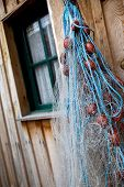 stock photo of wooden shack  - Fishing net hanging on a fisherman shack - JPG
