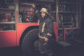 picture of fireman  - Fireman taking equipment from firefighting truck  - JPG