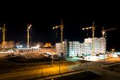 pic of construction crane  - high buildings under construction with cranes and illumination at night - JPG