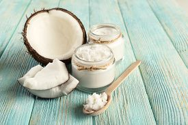 image of wooden table  - Fresh coconut oil in glassware and wooden spoon on color wooden table background - JPG