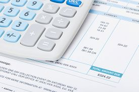 stock photo of calculator  - Neat calculator with utility bill under it - JPG