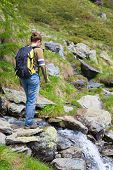 stock photo of italian alps  - Female hiker with backpack crossing little stream in the mountains - JPG