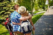 image of amor  - Amorous couple with backpacks walking in urban environment - JPG