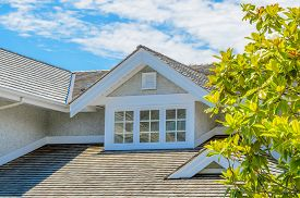 stock photo of red roof  - The roof of the house with nice window - JPG