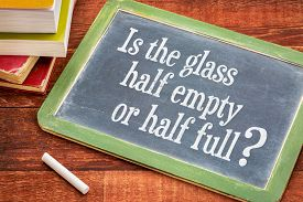 picture of half  - Is the glass half empty or half full question on a slate blackboard with a white chalk and a stack of books against rustic wooden table - JPG