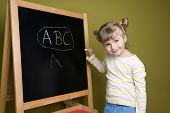 Cute little girl at blackboard