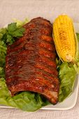 Slab Of Ribs Resting On Lettuce With An Ear Of Roasted Corn