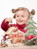 Little girl decorating oneself made Christmas cookies house
