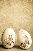 two Easter decorated eggs over grunge background in sepia tonality