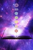 seven symbols of chakra with a book over a starry Universe like a concept for lesson of reiky, chakr