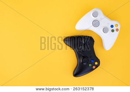 poster of Black And White Joystick On A Yellow Background. White And Black Gamepad Is Isolated On A Yellow Bac