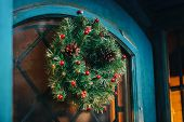 Traditional Christmas Wreath With Red Berries And Pine Cones On Old Blue Door In European City Stree poster