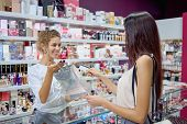 Positive Female Seller Giving Purchase To Elegant Customer In Cosmetics Store. Young Brunette Buying poster