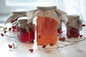 Autumn canning: jars with jam on a wooden table