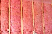 Bats of pink fiberglass insulation used in home construction to conserve heat and add energy efficiency.
