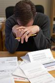pic of paycheck  - man in despair over bills - JPG